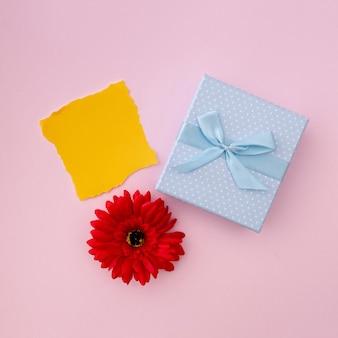 Bild des schrottes des gelben papiers mit einem blauen geschenk