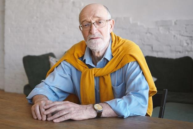 Bild des selbstbewussten erfolgreichen attraktiven geschäftsmannes in seinen sechzigern, der am hölzernen schreibtisch im modernen büroinnenraum sitzt und ernsten gesichtsausdruck hat. menschen, lebensstil, altern, geschäft und mode