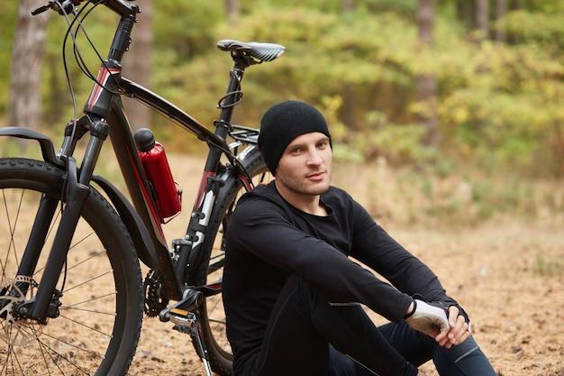 Bild des selbstbewussten gutaussehenden modells, das über fahrrad aufwirft, sich entspannt und freizeit genießt, sport treibt und frische luft atmet