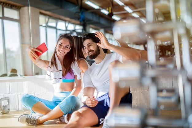 Bild des sportlichen schönen passenden paares, das im hellen fitnessstudio sitzt und foto von ihnen selbst macht. lächeln und telefon ansehen.