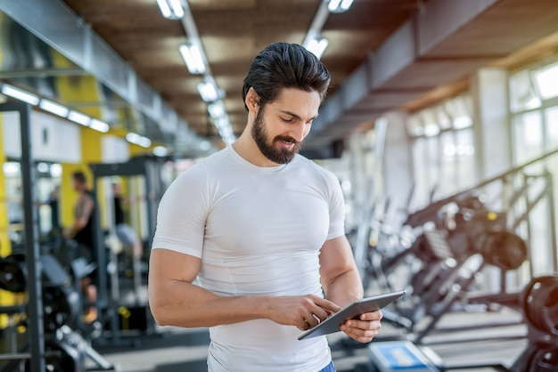 Bild des starken gutaussehenden persönlichen fitnesstrainers, der vor der kamera im hellen fitnessstudio aufwirft.