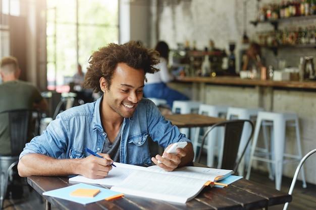 Bild des stilvollen afrikanischen studenten mit dem ohrring, der das jeanshemd trägt, das am hölzernen tisch sitzt, der seine hausaufgaben hält, die smartphone halten, das glücklich ist, nachricht von seinem freund zu erhalten, der etwas tippt