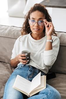 Bild des stilvollen afroamerikanermädchens, das buch liest und tee trinkt, während auf sofa in der hellen wohnung sitzt