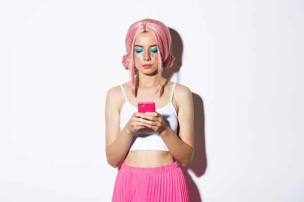 Bild des stilvollen glamourmädchens in der rosa perücke, das handy ernst betrachtet, im party-outfit stehend.