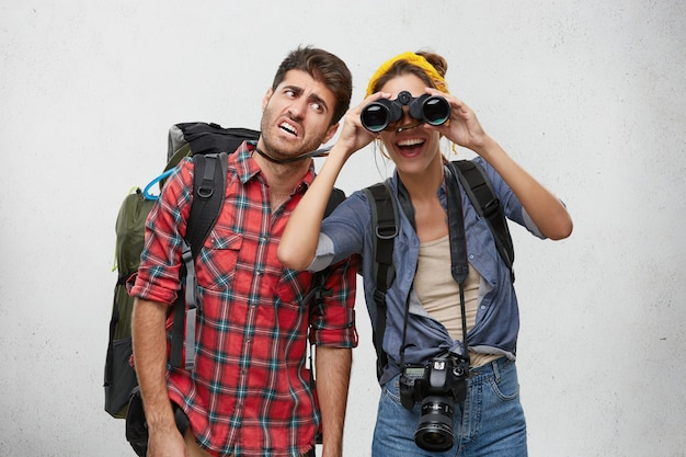 Bild des touristen des müden bärtigen mannes, der schweren rucksack und fröhliche aufgeregte frau mit fotokamera trägt, die nach platz für camping unter verwendung des fernglases während der wanderreise zusammen sucht. menschen und abenteuer
