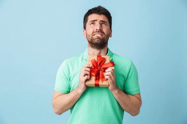 Bild des traurigen jungen gutaussehenden bärtigen mannes, der lokalisiert über der blauen wand aufwirft, die gegenwärtige geschenkbox hält.