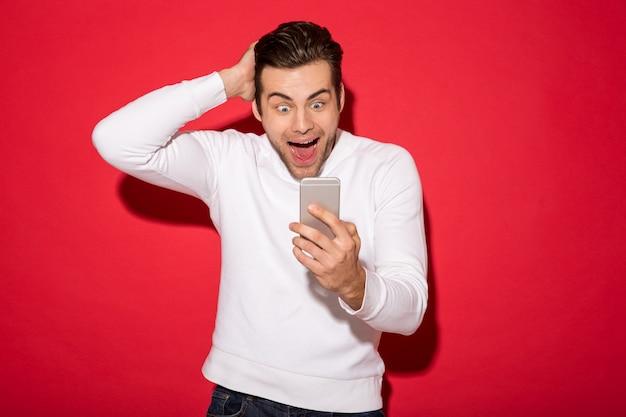 Bild des überraschten glücklichen mannes in der strickjacke, die smartphone über roter wand betrachtet