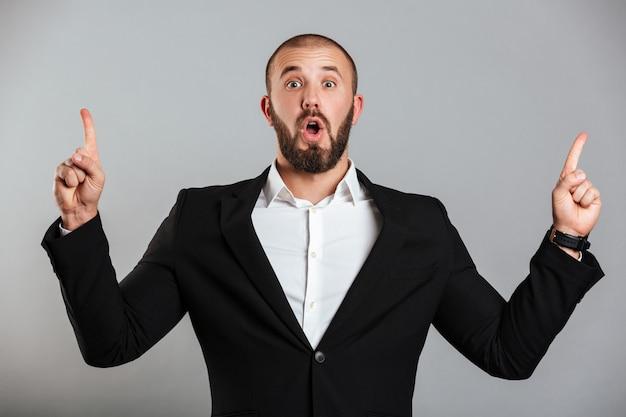 Bild des überraschten kaukasischen mannes im schwarzen geschäftsanzug, der auf kamera aufwirft und finger nach oben auf kopienraum zeigt, lokalisiert über graue wand
