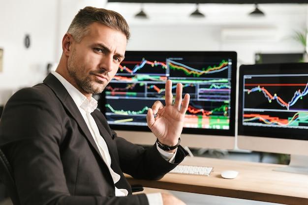 Bild des unrasierten geschäftsmanns 30s, der anzug trägt, der im büro am computer mit grafiken und diagrammen am bildschirm arbeitet