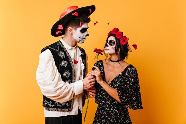 Bild des verliebten paares, das rose hält. mann und frau mit gesichtskunst schauen sich sanft in die augen.