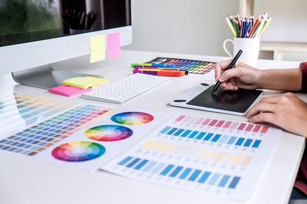 Bild des weiblichen kreativen grafikdesigners, der an farbauswahl arbeitet und auf grafiktablette zeichnet
