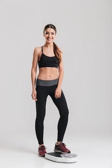 Bild des weiblichen sporttrainers in voller länge, der ihr gewicht nach der fitness misst, die auf skala, lokalisiert über grauer wand steht