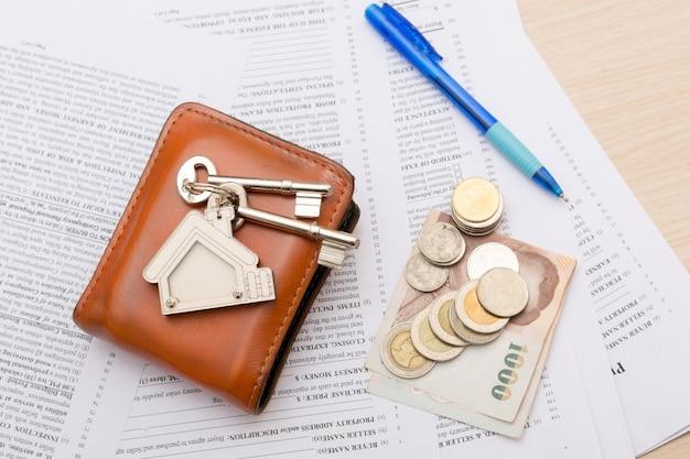Bild des wohnmietvertrags mit geld und schlüsseln. unterzeichneter vertrag und schlüssel des eigentums mit dokumenten. konzept für das immobiliengeschäft.