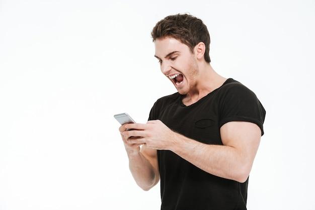 Bild des wütenden schreienden jungen mannes in schwarzem t-shirt, der auf weißem hintergrund steht und das telefon benutzt.