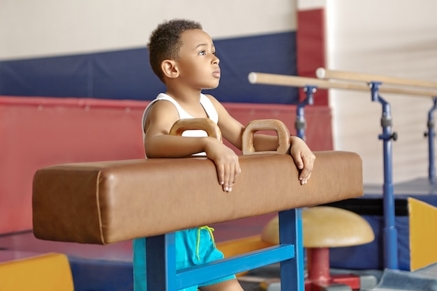 Bild des zehnjährigen afroamerikanischen kindes im weißen t-shirt, das durch pauschenpferd im fitnessstudio steht