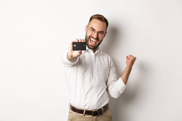 Bild des zufriedenen geschäftsmannes, der kreditkarte zeigt, faustpumpe in der freude macht, stehend