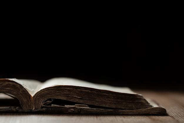 Bild einer alten heiligen bibel auf hölzernem hintergrund in einem dunklen raum