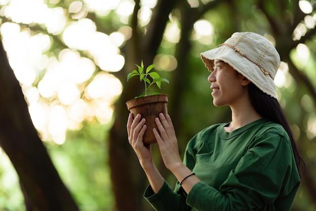 Bild einer asiatischen frau im konzept des pflanzens von bäumen für die umwelt