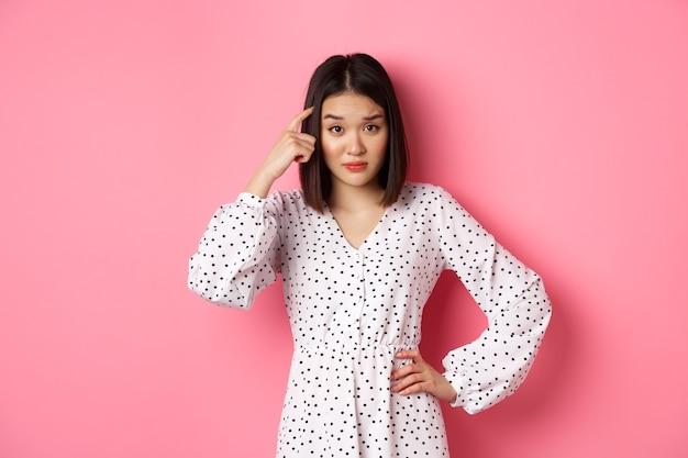 Bild einer attraktiven asiatischen dame, die person schimpft, auf den kopf zeigt und enttäuscht auf die kamera starrt, bist du dumme geste, die auf rosafarbenem hintergrund steht.