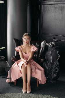 Bild einer charmanten kaukasischen dame sitzt auf dem schwarzen ledersessel und posiert für die kamera