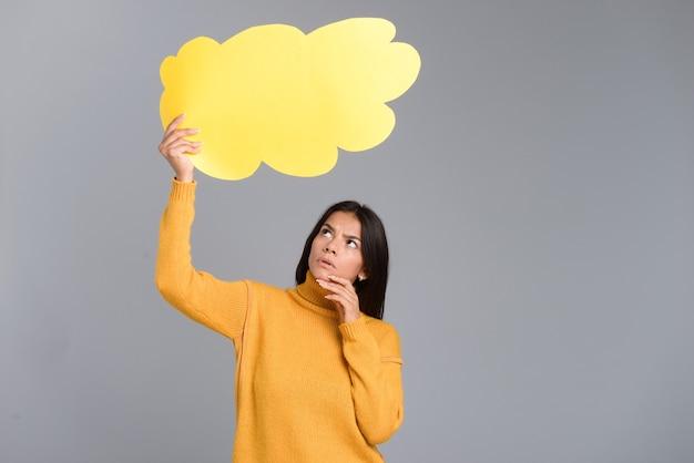 Bild einer denkenden frau, die lokalisiert über graue wand darstellt, die gedankenblase hält.