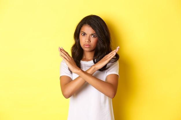 Bild einer enttäuschten und wütenden afroamerikanischen frau, die nein sagt, ein stoppschild zeigt und die stirn runzelt, verbietet und widerspricht ihnen, steht auf gelbem hintergrund.