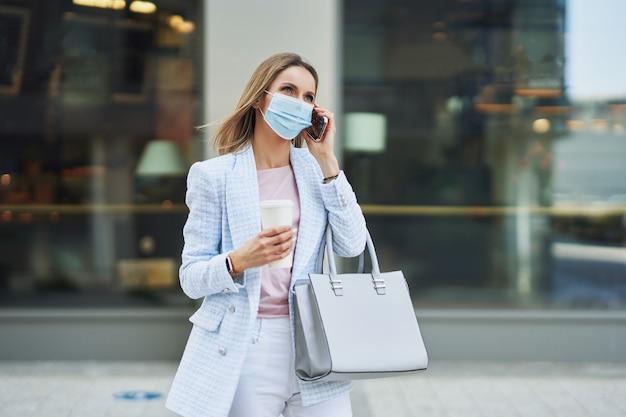 Bild einer erwachsenen attraktiven frau, die eine maske mit smartphone trägt, die in der stadt spazieren geht