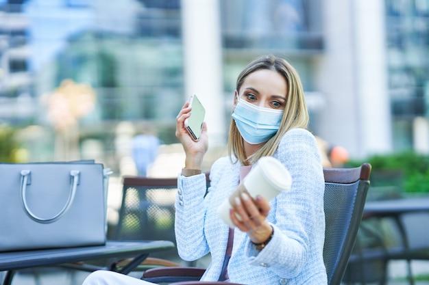 Bild einer erwachsenen attraktiven frau mit maske, die kaffee in der stadt trinkt