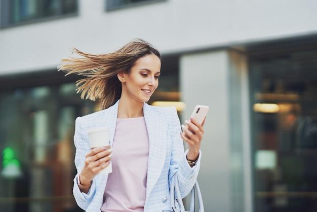 Bild einer erwachsenen attraktiven frau mit smartphone, die in die stadt geht