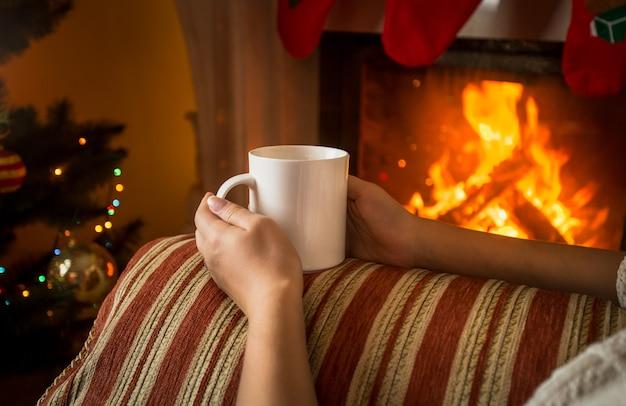 Bild einer frau, die auf dem sofa am kamin sitzt und eine tasse tee hält