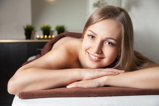 Bild einer frau im spa-salon, die auf dem massagetisch liegt