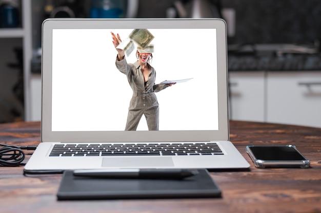 Bild einer frau in einem anzug mit einem tablet. sie wirft dollar und lacht. erfolgskonzept.