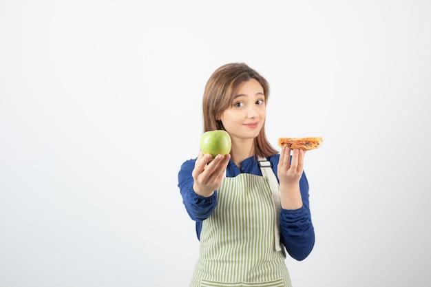 Bild einer frau in schürze, die versucht zu wählen, was sie apfel oder pizza essen soll?