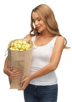 Bild einer frau mit einer einkaufstüte voller äpfel