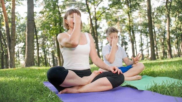 Bild einer frau mittleren alters, die teenager unterrichtet, die yoga und fitness auf gras im park macht. familie kümmert sich um ihre gesundheit