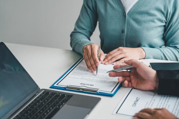 Bild einer frauenhand, die auf ein dokument über die bewerbung um eine stelle an den vorgesetzten im büro zeigt.