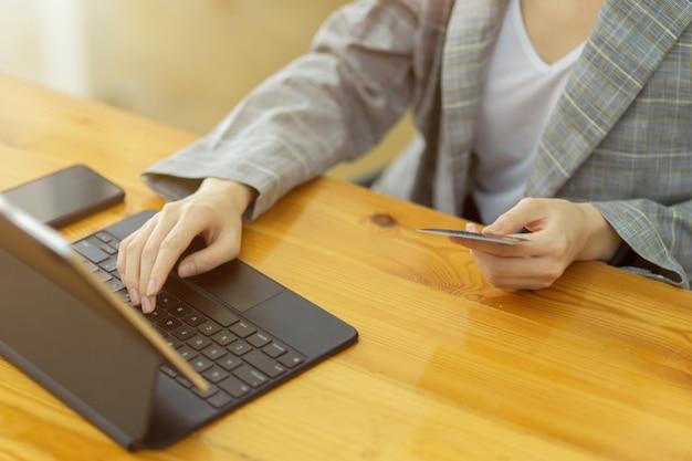 Bild einer freiberuflerin zuschneiden, die kreditkarte hält und auf der tablettastatur tippt