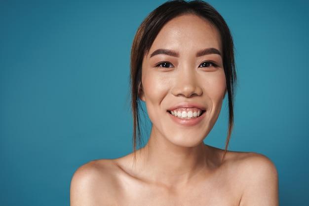 Bild einer fröhlichen glücklichen asiatischen frau, die nackt auf blauer wand lokalisiert aufwirft.