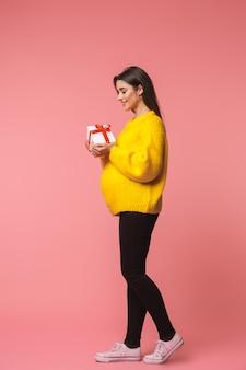 Bild einer fröhlichen jungen schwangeren emotionalen frau, die lokalisiert über rosa haltegeschenkbox aufwirft.