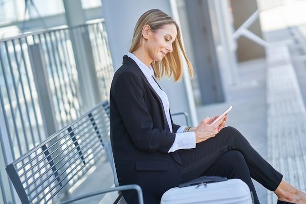 Bild einer geschäftsfrau, die im bahnhof sitzt und wartet