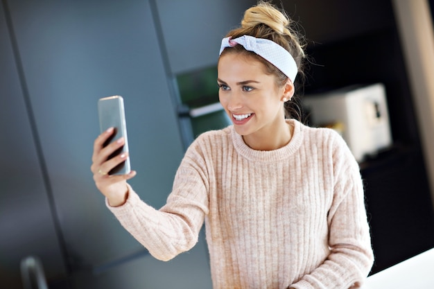 Bild einer glücklichen frau, die in der küche eine sms schreibt