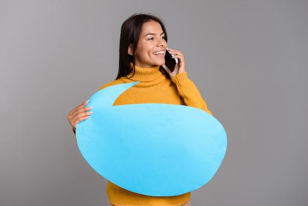 Bild einer glücklichen frau, die lokalisiert über graue wandwand hält, die sprachblase hält, die durch telefon spricht.
