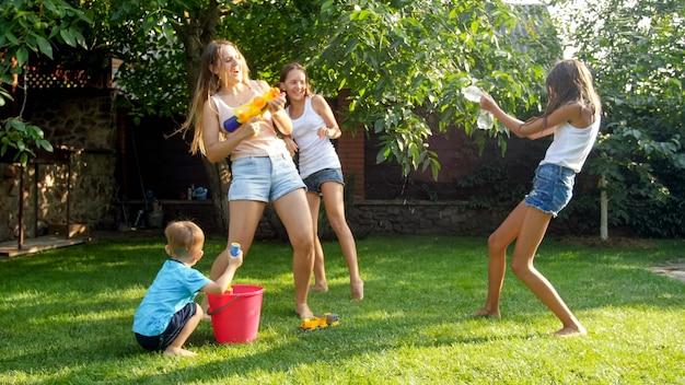 Bild einer glücklichen, fröhlichen familie, die im hinterhofgarten spielt. leute, die mit wasserpistolen und gartenschlauch wasser spritzen.