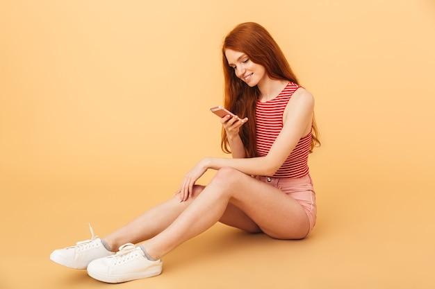 Bild einer glücklichen fröhlichen jungen schönen rothaarigen frau, die lokalisiert über gelber wand mit handy aufwirft.