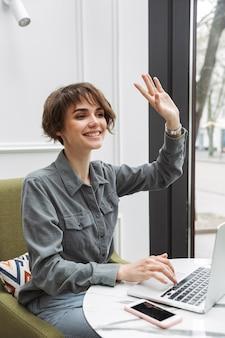Bild einer glücklichen jungen hübschen geschäftsstudentenfrau, die im café zuhause sitzt und laptop-computer coworking verwendet, die zu freunden wellenartig bewegt.
