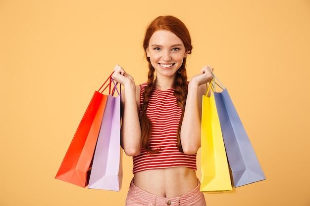 Bild einer glücklichen jungen schönen rothaarigen frau, die lokalisiert über gelber wand aufwirft, die einkaufstaschen hält.