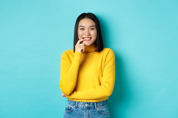 Bild einer gut aussehenden asiatischen frau in stilvollem outfit, die die lippe berührt und mit glücklichem gesicht in die kamera lächelt und auf blauem hintergrund steht.