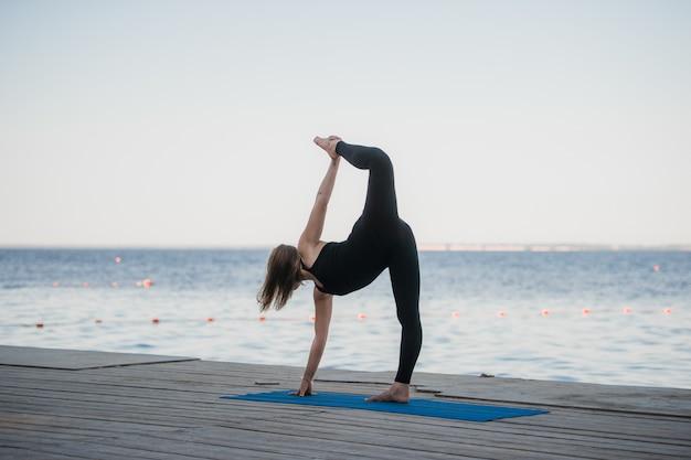 Bild einer hübschen frau, die yoga am see tut