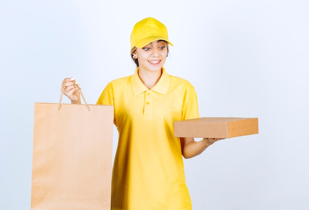 Bild einer hübschen frau in gelber uniform, die braune leere kraftpapierbox und tasche hält.