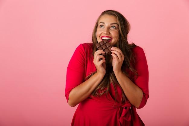 Bild einer hübschen hungrigen jungen frau lokalisiert über rosa wand, die schokolade hält.